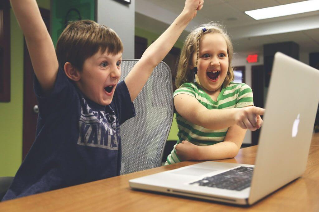children cheering at a video game on a laptop